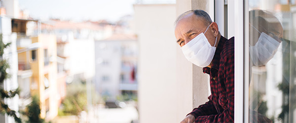 Senior man in medical mask on window breathing fresh air from quarantine.