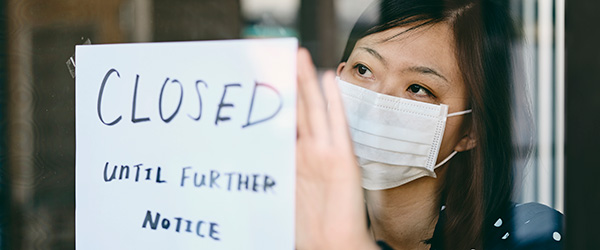 Woman wearing mask posts sign on door that says Closed Unitil Further Notice.